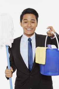 Businessman holding up a mop and other cleaning supplies